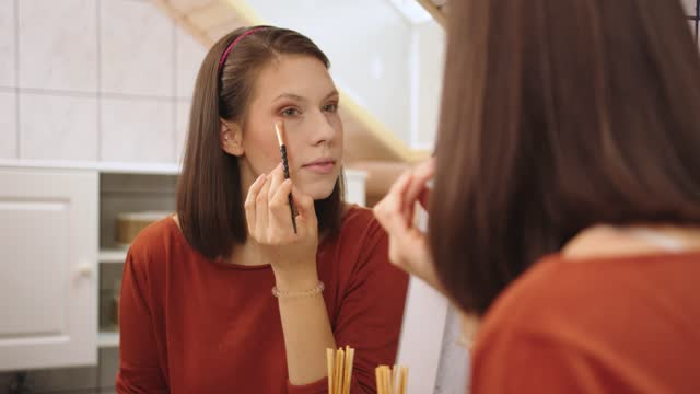 beautiful young woman doing her make up, applying eyeshadow with a brush - caucasian appearance stock videos & royalty-free footage