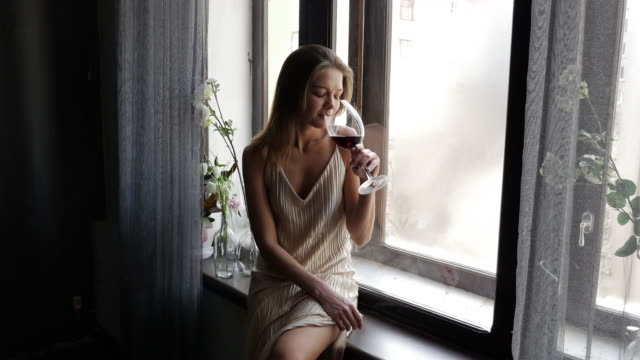 Beautiful young woman drinking a glass of wine while sitting on the windowsill