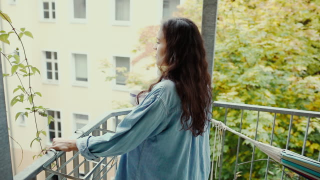 beautiful young woman drinking coffee barefoot, wearing an oversized denim shirt in morning on balcony in typical old apartment building in berlin, germany. - balcony stock videos & royalty-free footage