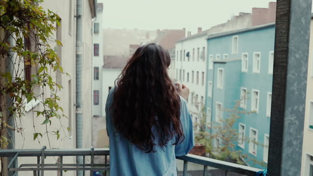 beautiful young woman drinking coffee barefoot, wearing an oversized denim shirt in morning on balcony in typical old apartment building in berlin, germany. - coffee drink stock videos & royalty-free footage