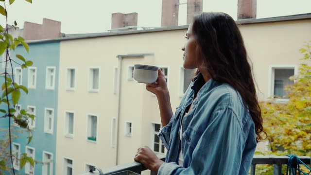 stockvideo's en b-roll-footage met beautiful young woman drinking coffee barefoot, wearing an oversized denim shirt in morning on balcony in typical old apartment building in berlin, germany. - enjoyment