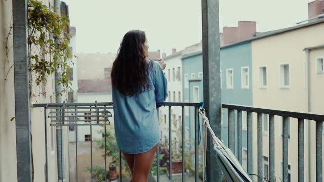 Beautiful young woman drinking coffee barefoot, wearing an oversized denim shirt in morning on balcony in typical old apartment building in Berlin, Germany.