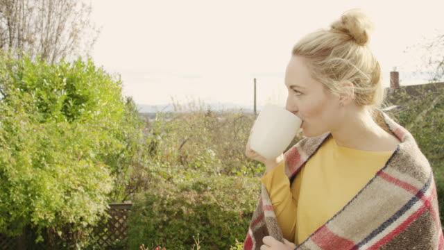 Schöne junge Frau Kaffeetrinken im Freien in eine Decke gehüllt