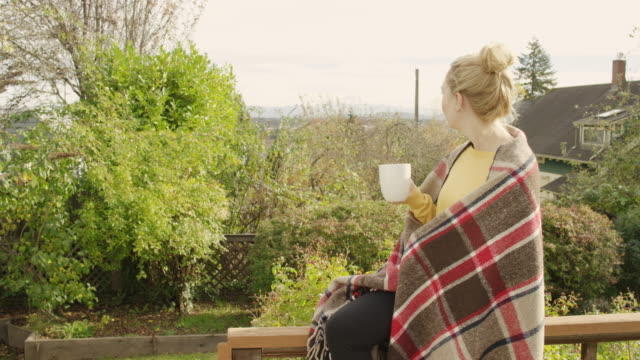 beautiful young woman drinking coffee outdoors wrapped in a blanket - fatcamera stock videos & royalty-free footage