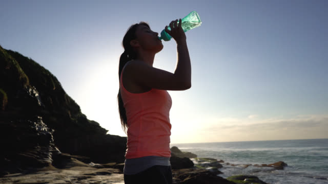 Beautiful young woman drinking water after exercising while enjoying the view at the beach