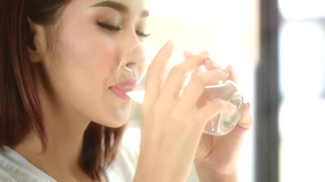 beautiful young woman drinking water is healthy smiling
