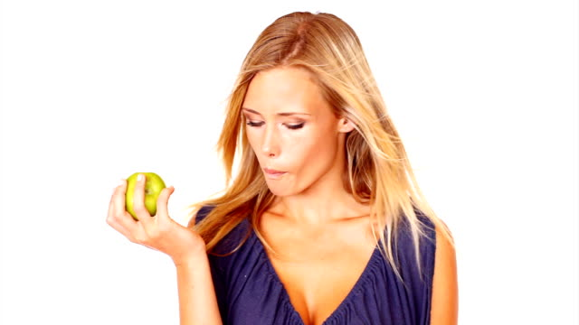 beautiful young woman eating an apple - plain background stock videos & royalty-free footage