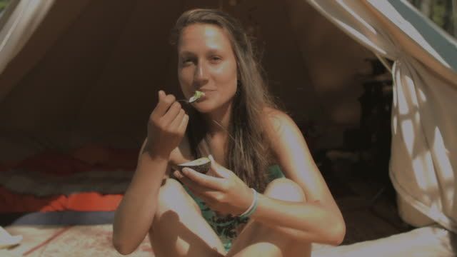 Beautiful young woman eating avocado in front of tent in sunshine at Atlantic coast in South of France in summer