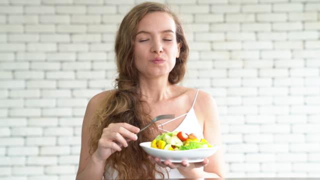 Eine schöne junge Frau essen Salat