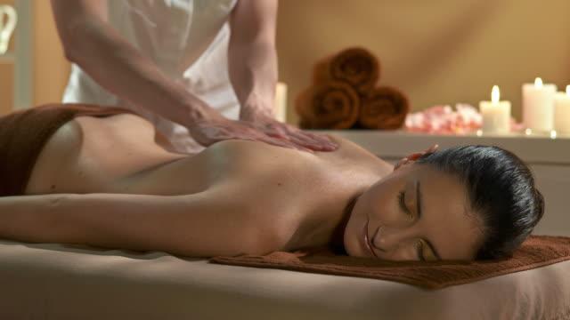 vidéos et rushes de hd: belle jeune femme appréciant un massage à l'huile - massage table