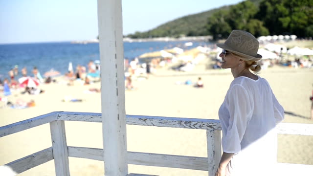 beautiful young woman enjoys sun on her vacation. - sun hat stock videos & royalty-free footage