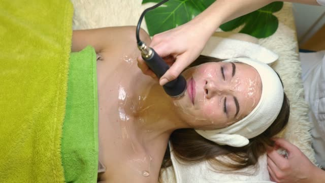 vídeos de stock e filmes b-roll de beautiful young woman enyoing her facial treatment - cuidado com o corpo