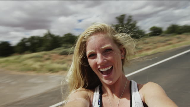 beautiful young woman films selfie spinning with joy in nature. - customized stock videos and b-roll footage