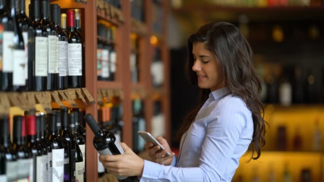 Beautiful young woman grabbing a wine bottle from the shelf and scanning the bar code on a wine application on her smartphone