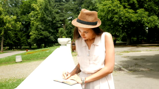 beautiful young woman hand writing in her diary outdoors - diary stock videos & royalty-free footage