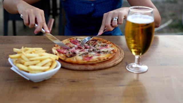 vídeos y material grabado en eventos de stock de hermosa joven pasando el rato y comiendo pizza y patatas fritas, bebiendo cerveza. - modales de mesa