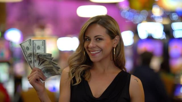 vidéos et rushes de belle jeune femme tenant un tas d'argent tout en regardant la caméra très ludique - casino