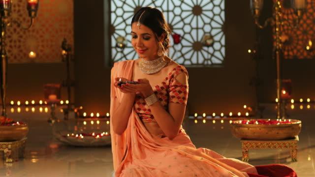 MS Beautiful young woman holding a diya during Diwali festival / New Delhi, Delhi, India