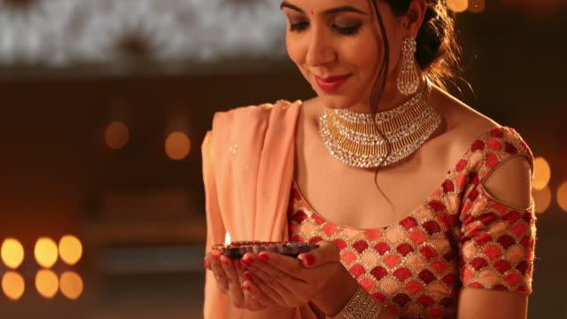 cu tu beautiful young woman holding a diya during diwali festival / new delhi, delhi, india - jewellery stock videos & royalty-free footage