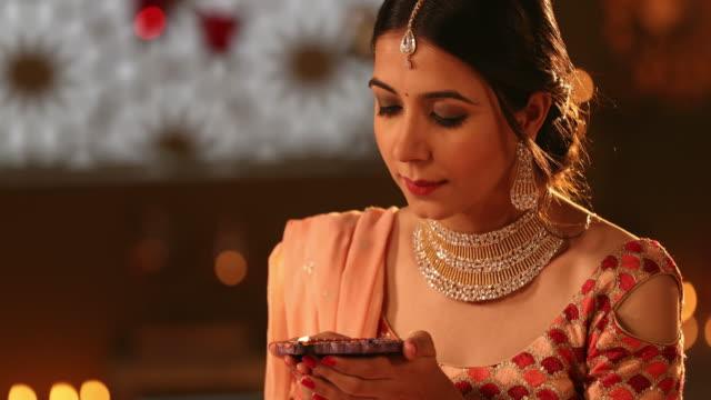 vídeos y material grabado en eventos de stock de cu beautiful young woman holding a diya during diwali festival / new delhi, delhi, india - manos ahuecadas