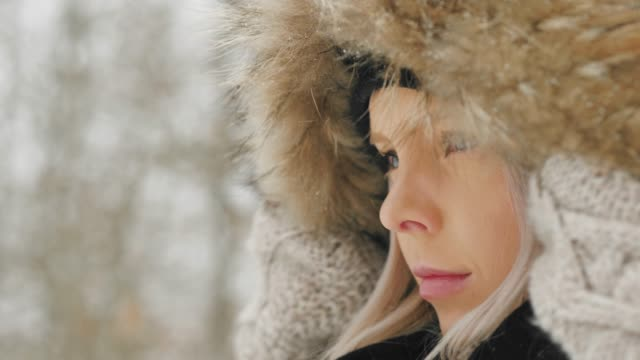 beautiful young woman in a cozy parka on a snowy winter day - coat stock videos & royalty-free footage