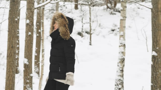 beautiful young woman in a cozy parka on a snowy winter day - mitten stock videos and b-roll footage