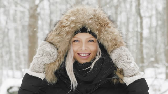vacker ung kvinna i en mysig parkas en snöig vinterdag - huva bildbanksvideor och videomaterial från bakom kulisserna