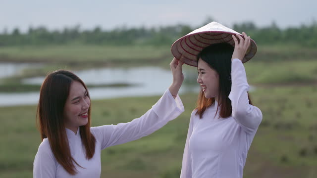 a beautiful young woman in a southeast asian teen wearing a white dress, holding a bamboo weave hat. stood laughing for the camera in a good mood - white dress stock videos & royalty-free footage