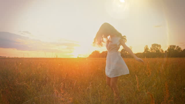 slo mo beautiful young woman in a white dress twirling in the grass at sunset - dress stock videos & royalty-free footage