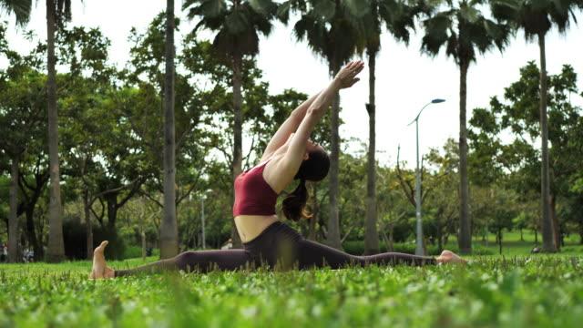 stockvideo's en b-roll-footage met mooie jonge vrouw in azië oefening yoga en splitsen benen - lotuspositie