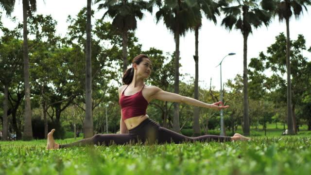 stockvideo's en b-roll-footage met mooie jonge vrouw in azië oefening yoga en stretching haar lichaamsdelen - lotuspositie