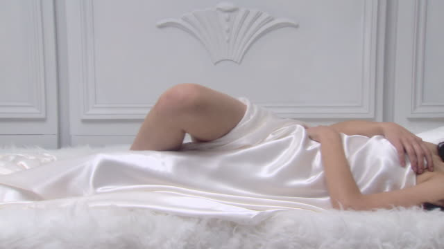 stockvideo's en b-roll-footage met beautiful young woman in bed - halfgekleed