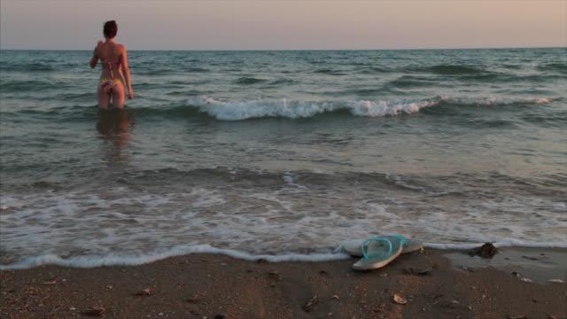 vídeos de stock, filmes e b-roll de beautiful young woman in bikini on the beach. - coque cabelo para cima