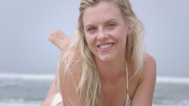 beautiful young woman in bikini smiles at camera while sunbathing 4k - vesper stock stock videos & royalty-free footage