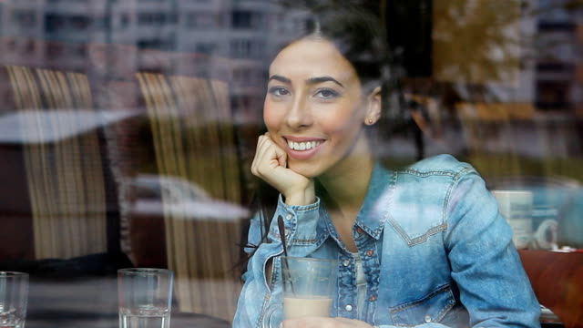 vídeos y material grabado en eventos de stock de hermosa mujer joven en cafe - mano en la barbilla