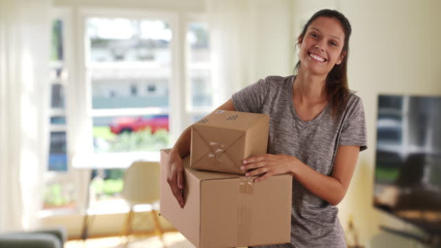 vídeos y material grabado en eventos de stock de beautiful young woman in living room carrying shipping boxes - recibir