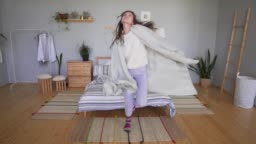Beautiful young woman in pajamas and a sweater is dancing and having fun next to the bed, hiding in a blanket in the bedroom. Hygge or Lagom concept