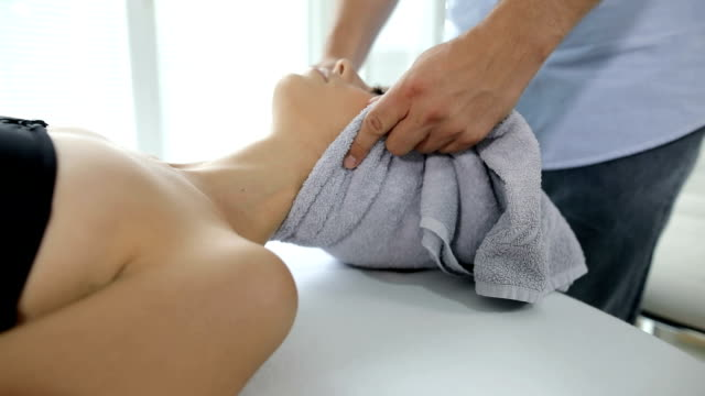 beautiful young woman in spa salon getting massage - chiropractic adjustment stock videos & royalty-free footage