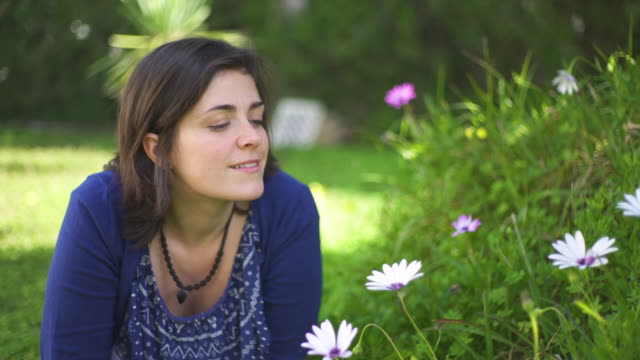 stockvideo's en b-roll-footage met beautiful young woman in the garden smiling and smelling the flowers - silvestre