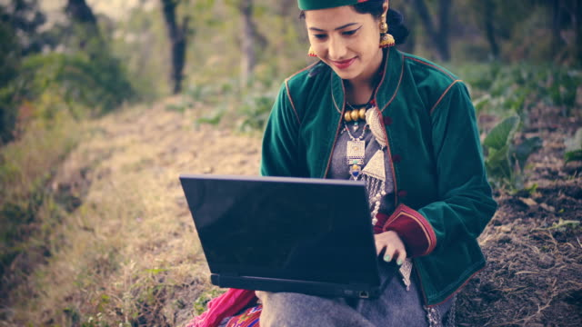 Beautiful young woman in traditional dress of Kinnaur using laptop.