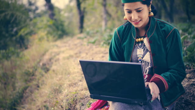 beautiful young woman in traditional dress of kinnaur using laptop. - earring stock videos & royalty-free footage