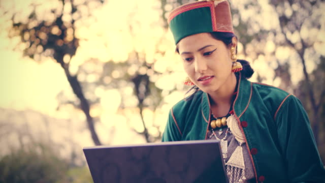 Beautiful young woman in traditional dress of Kinnaur using laptop.