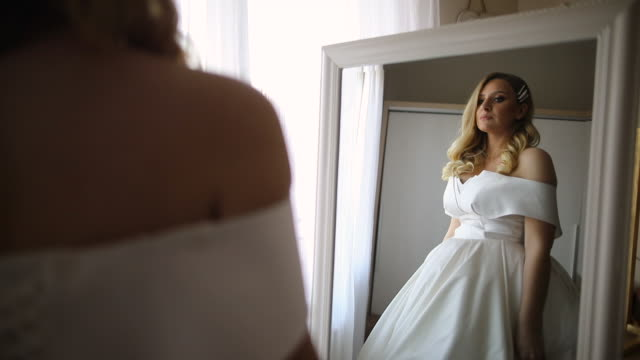 beautiful young woman in wedding dress standing in front of the mirror, looking at her self and smiling - hairstyle stock videos & royalty-free footage