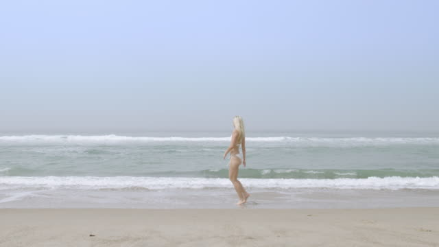 vídeos de stock, filmes e b-roll de beautiful young woman in white bikini paddles and splashes in malibu surf 4k - swimwear