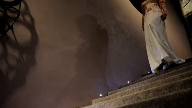 stockvideo's en b-roll-footage met mooie jonge vrouw in witte jurk lopend onderaan de stappen - jurk