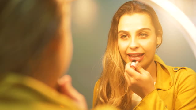 A beautiful young woman is in make-up in front of the mirror with lipstick