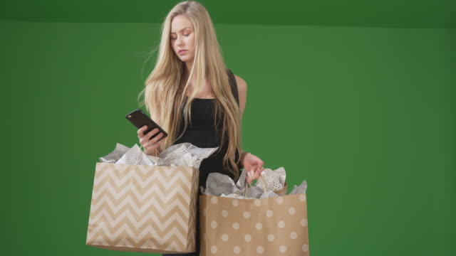 beautiful young woman late-night shopping for girlfriend presents on green screen - fashionable stock videos & royalty-free footage