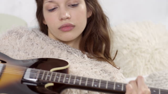 beautiful young woman lies on bed with electric guitar - plays and sits up - lying on back stock videos and b-roll footage
