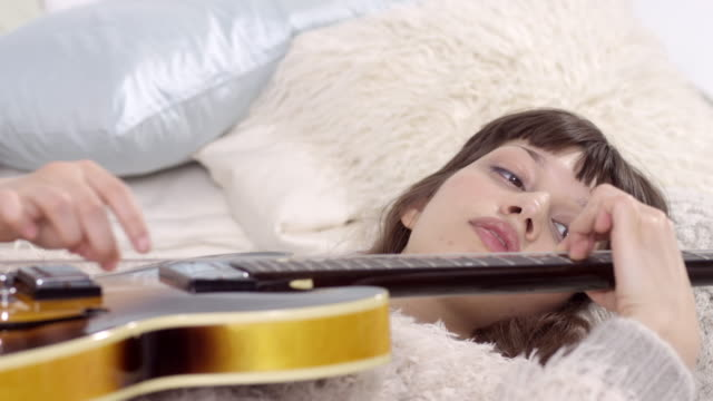 beautiful young woman lies on bed with electric guitar - plays/composes