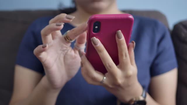 vidéos et rushes de belle jeune femme regardant son smartphone, et regardant la télévision. - photo messaging
